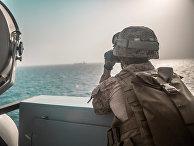 Американский военный смотрит в бинокль на корабль в Ормузском проливе