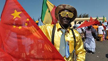 Сенегалец машет китайским флагом в Дакаре