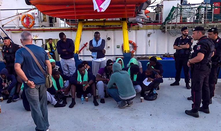 Мигранты высаживаются с судна Sea-Watch 3 в итальянском порту Лампедуза