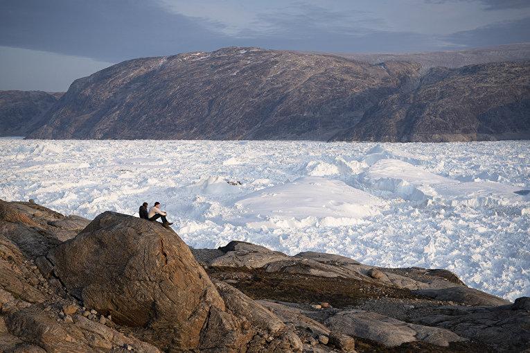 16 августа 2019. Студенты Нью-Йоркского университета сидят навершине скалы и любуютсягренландским ледником Хельхейм