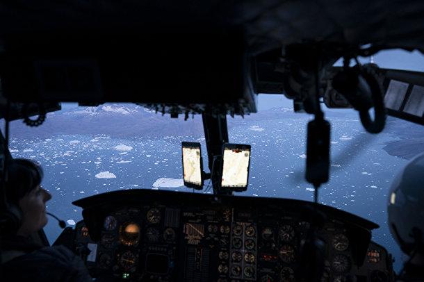 16 августа 2019. Вертолет пролетает над айсбергами вблизи ледника Хельхейм, Гренландия