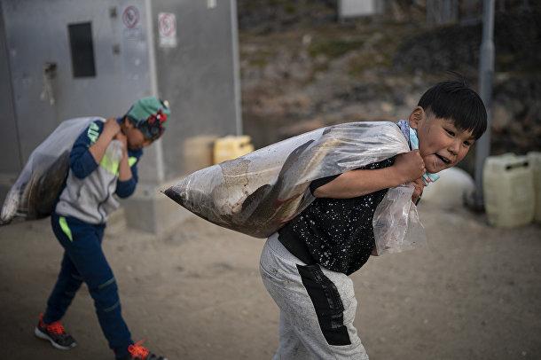Мальчики тащат пластиковые мешки срыбой, Кулусук, Гренландия