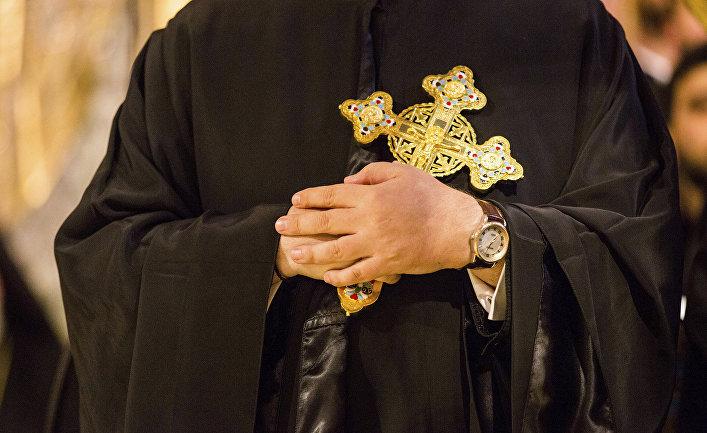 Греческий православный священнослужитель держит крест в архиепископском соборе Святой Троицы в Нью-Йорке