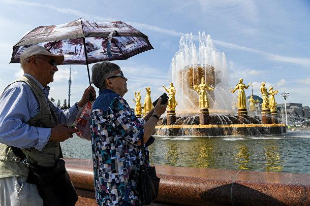 Пожилая пара у знаменитого фонтана Дружбы Народов на ВДНХ в Москве