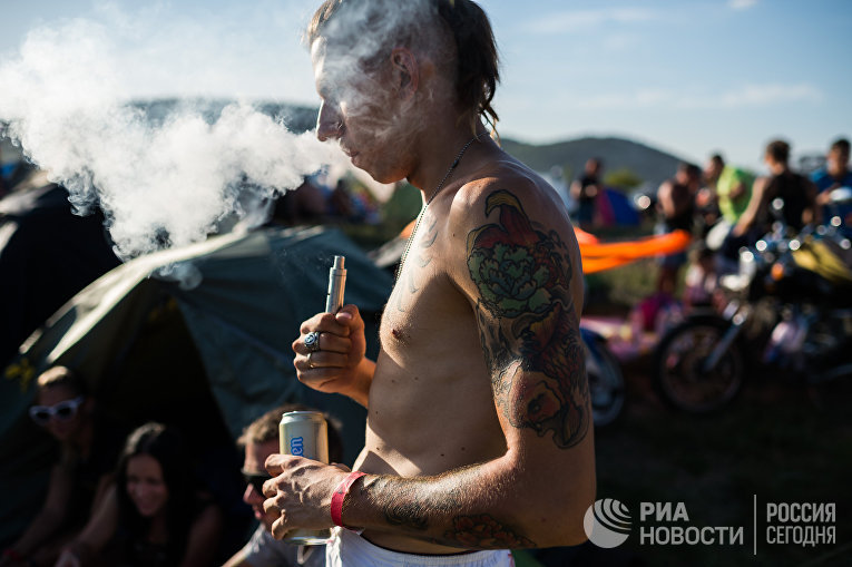 Мужчина курит вейп на байк-шоу