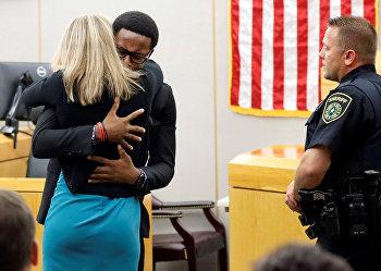 Младший брат убитого обнимает бывшего сотрудника полиции Далласа Эмбер Гайгер на замедании суда в Далласе, штат Техас, США