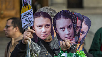 Маски Греты Тунберг во время акции протеста против изменения климата в Сантьяго, Чили