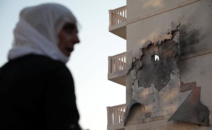 Женщина у дома, который был поврежден ракетой, выпущенной с территории Сирии в Нусайбине
