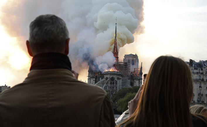 Люди наблюдают как пламя охватывает крышу Собора Парижской Богоматери в Париже