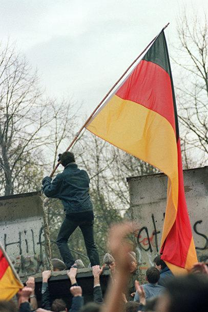 Житель Западного Берлина передает флаг через Берлинскую стену 11 ноября 1989 года