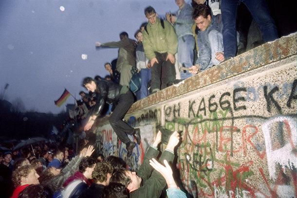 Жители Восточной Германии приветствуют граждан Западной Германии у Бранденбургских ворот в Берлине 22 декабря 1989 года