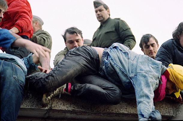 Берлинцы перелезают через Берлинскую стену 11 ноября 1989 года