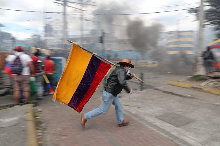 Демонстрант держит флаг Эквадора во время протеста