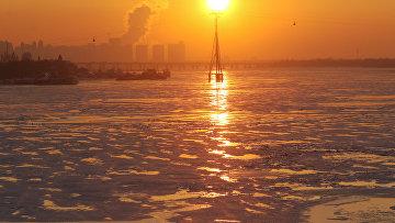 Заходящее солнце над замерзшей рекой Сонхуа в Харбине
