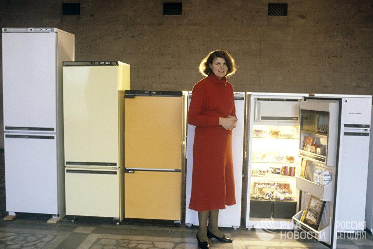 """Представитель производственного объединения по выпуску холодильников """"Атлант"""" рядом с образцами продукции"""