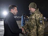 Президент Украины Владимир Зеленский приветствует украинского военного после обмена пленными в аэропорту Борисполь