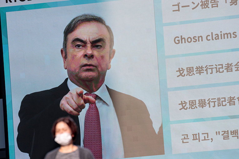 Бывший президент Nissan Карлос Гон на экране в Токио