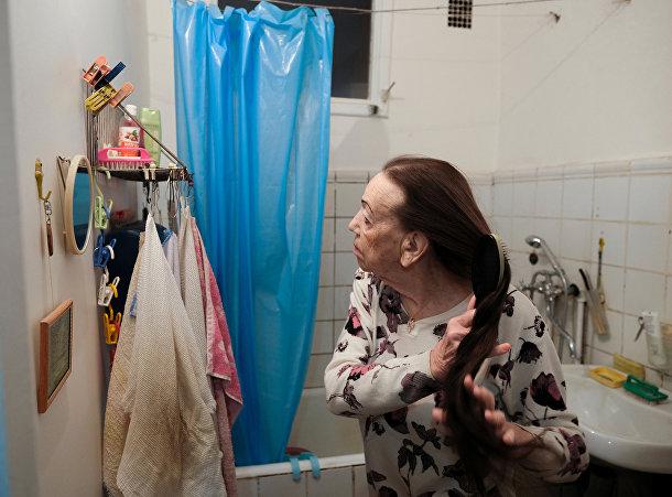 Майя Качина расчесывает волосы дома в Москве