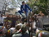 Лидер оппозиции Венесуэлы Хуан Гуайдо перелезает через забор, чтобы попасть в здание Национальной ассамблеи в Каракасе