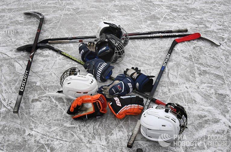 Клюшки, шлемы и перчатки на льду