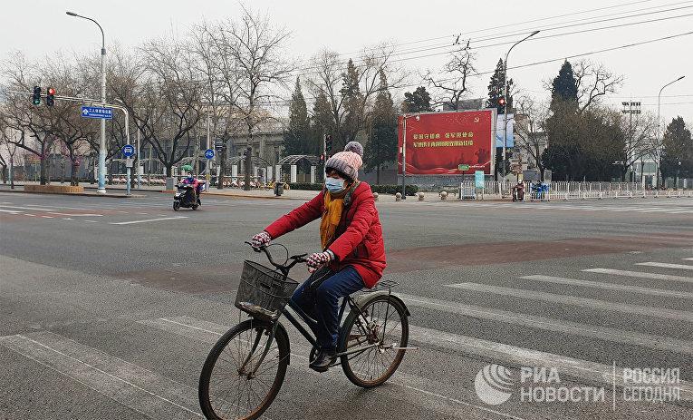 Девушка в медицинской маске едет на велосипеде по улице Пекина