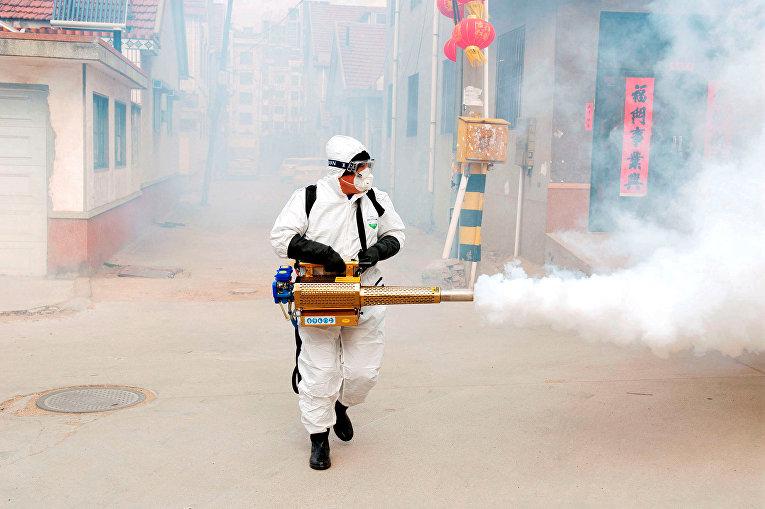 Рабочий в защитном костюме проводит дезинфекцию деревни Дунсинчжуан в Китае