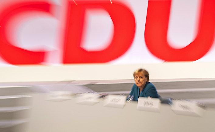 Канцлер Германии Ангела Меркель на фоне логотипа партии ХДС