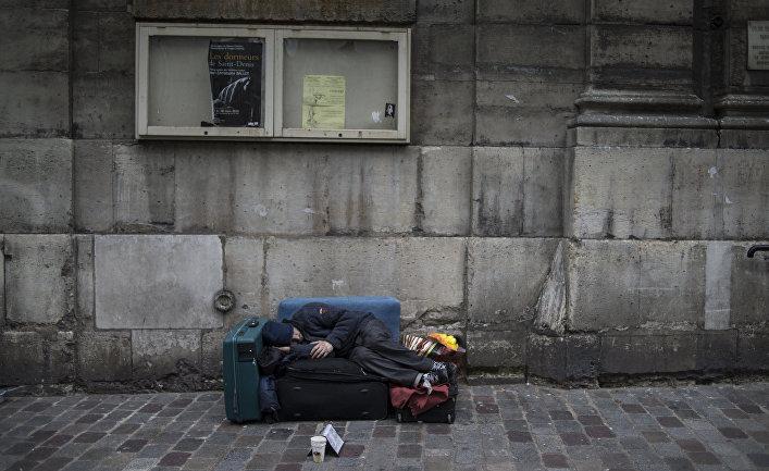Бездомный спит на одной из улиц Парижа