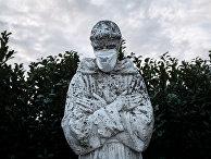 Маска на лице статуи в городе Сан-Фьорано, Италия