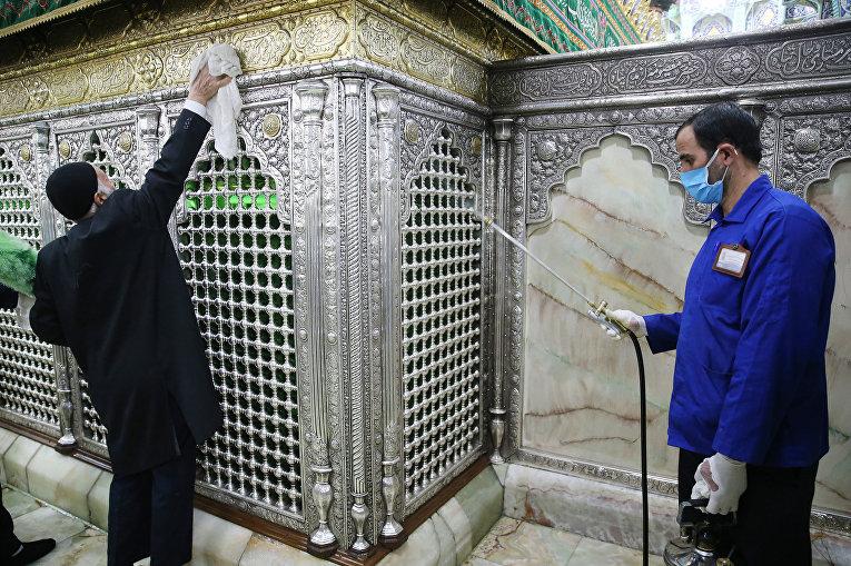 Работники проводят дезинфекцию храма Масуме в Куме, Иран