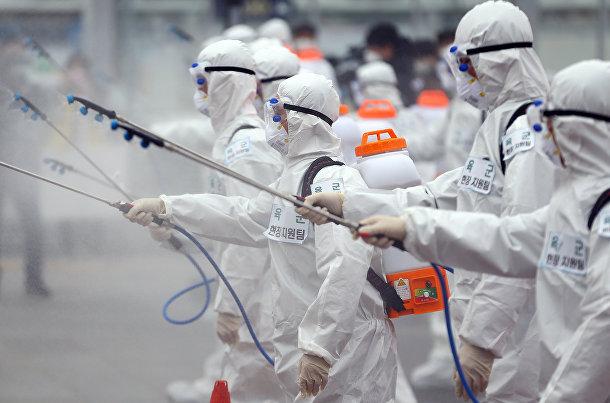 Южнокорейские солдаты в защитном снаряжении распыляют дезинфицирующее средство на железнодорожной станции в Тэгу