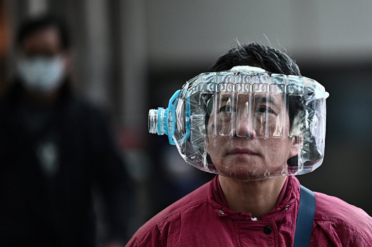 Мужчина с пластиковой бутылкой на голове в качестве меры защиты от коронавируса в Гонконге