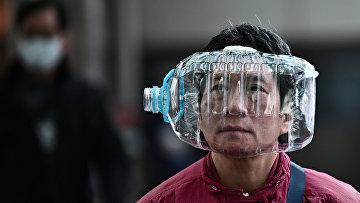 Мужчина с пластиковой бутылкой в качестве меры защиты от коронавируса в Гонконге