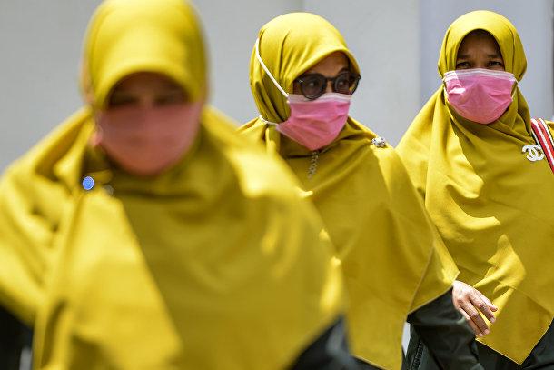 Женщины в медицинских масках в Банда-Ачех, Индонезия