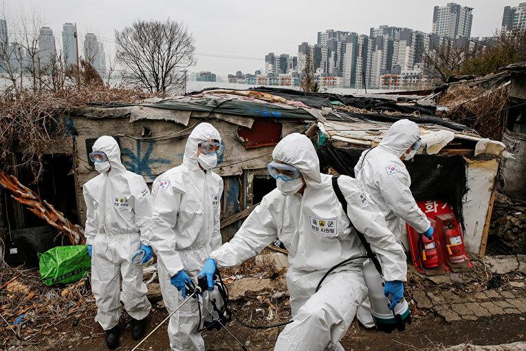 Южнокорейские солдаты в защитных костюмах дезинфицируют дома в бедном районе Сеула, Южная Корея