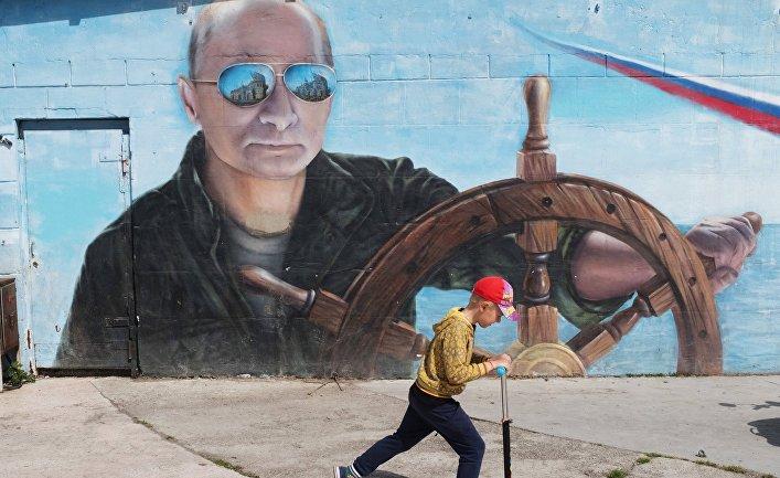 Мальчик проезжает на самокате рядом с граффити с изображением президента РФ Владимира Путина на набережной Ялты