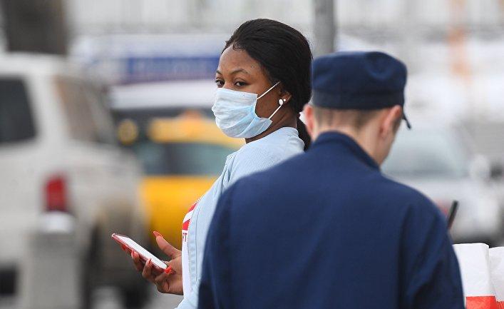 Девушка в защитной маске на одной из улиц в Москве