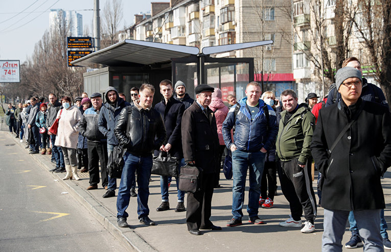Пассажиры на остановке общественного транспорта в Киеве, Украина