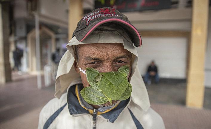 Уличный торговец в самодельной маске из фиговых листьев в Медине, Марокко
