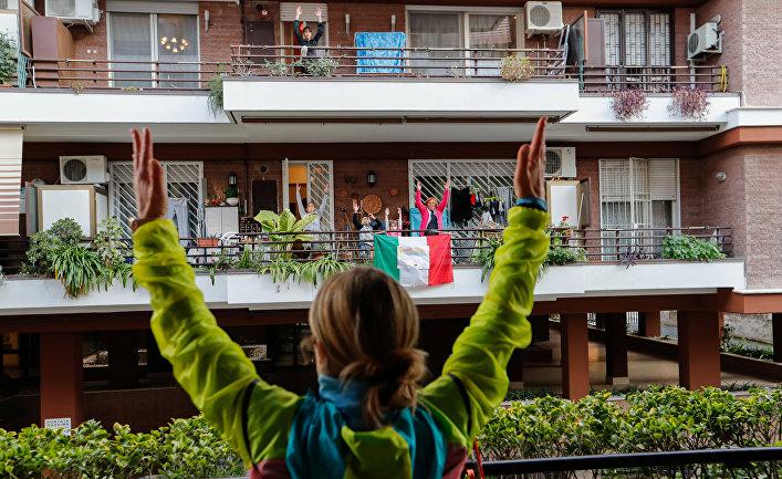 Тренер проводит с балкона занятия для сидящих в карантине соседей, Рим, Италия