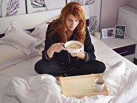 Девушка завтракает в кровати