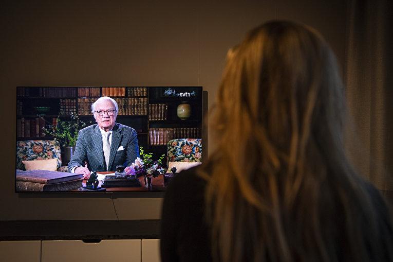 Женщина смотрит по телевизору обращение к нации короля Швеции Карла XVI Густава по поводу эпидемии коронавируса