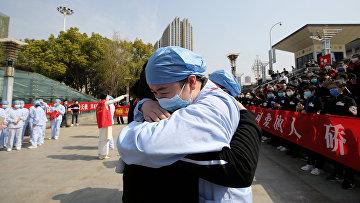 Медики обнимаются во время церемонии прощания с медицинской бригадой из Цзянсу на железнодорожном вокзале города Ухань, Китай