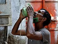 1 апреля 2020. Мужчина пьет воду в пригороде Мумбаи, Индия