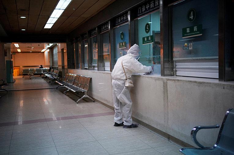 Женщина в защитном костюме в больнице в Ухане, Китай
