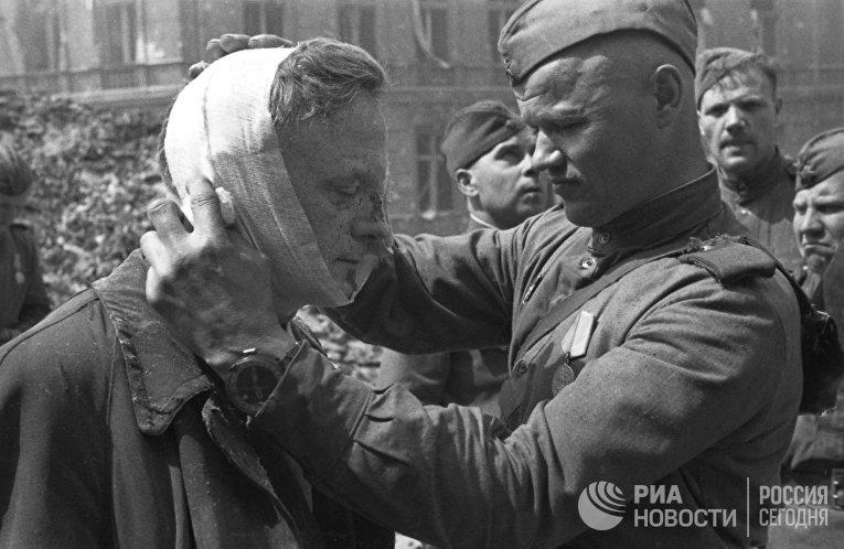 Великая Отечественная война 1941-1945 гг. Взятие Берлина Красной Армией. Советский солдат оказывает медицинскую помощь раненому местному жителю.