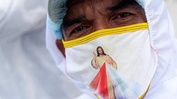 15 апреля 2020. Работник похоронной службы в маске с изображением Иисуса Христа, Гуаякиль, Эквадор
