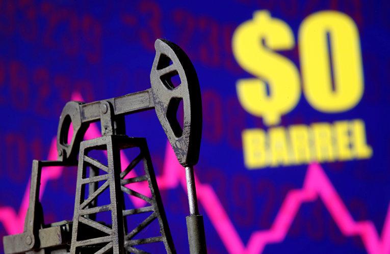 Муляж нефтяного насоса на фоне надписи «0 долларов за баррель»