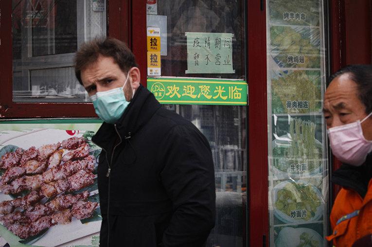 Иностранец на фоне закрытых магазинов в Пекине