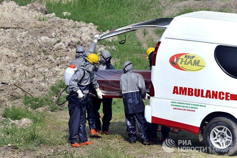 Офицеры и медики в защитных костюмах во время похорон человека, умершего от коронавируса, в Медане в Индонезии